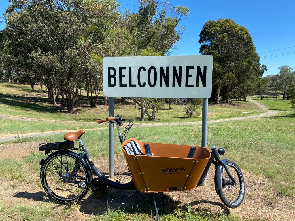 A Babboe cargo bike  parked in front of a Belconnen sign.